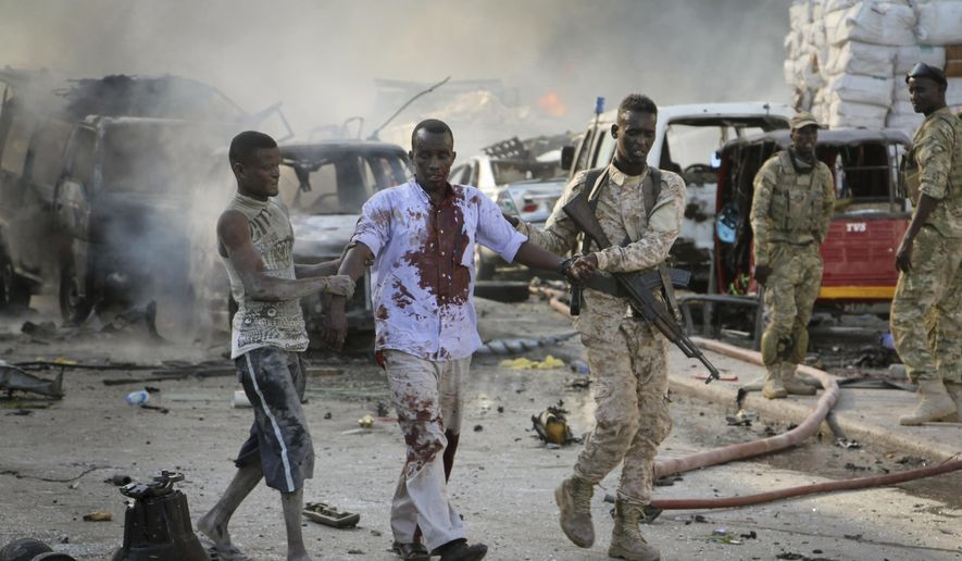 FILE-- In this Saturday, Oct 14, 2017, file photo, a soldier helps a civilian who was wounded in a blast in the capital of Mogadishu, Somalia. Somalia is marking the first anniversary of one of the world's deadliest attacks since 9/11, a truck bombing in the heart of Mogadishu that killed well over 500 people. The Oct. 14, 2017 attack was so devastating that the al-Shabab extremist group that often targets the capital never claimed responsibility amid the local outrage. As Somalis gather at a new memorial with a minute of silence, local media report that the man accused of orchestrating the bombing has been executed. (AP Photo/Farah Abdi Warsameh-File)