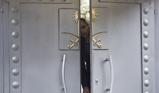 A security personnel looks out from the entrance of the Saudi Arabia's consulate in Istanbul, Sunday, Oct. 14, 2018. Writer Jamal Khashoggi, vanished after he walked into the consulate on Oct. 2. (AP Photo/Petros Giannakouris)