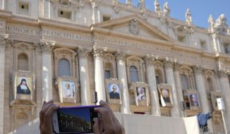 A woman takes photos of tapestries of Roman Catholic Archbishop Oscar Romero, 3rd from left, and Pope Paul VI, 4th from left, hanging from a balcony of the facade of St. Peter's Basilica at the Vatican, Saturday, Oct. 13, 2018. Pope Francis will canonize two of the most important and contested figures of the 20th-century Catholic Church, declaring Pope Paul VI and the martyred Salvadoran Archbishop Oscar Romero as models of saintliness for the faithful today. (AP Photo/Andrew Medichini)