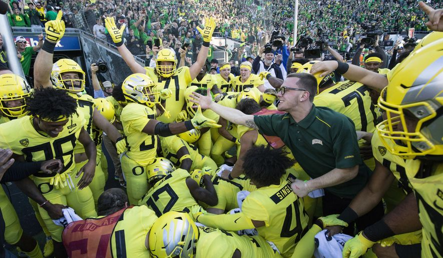 Oregon running back CJ Verdell (34), reaches out to an unidentified fan after scoring the winning touchdown in overtime to beat Washington 30-27 in an NCAA college football game in Eugene, Ore., Saturday, Oct. 13, 2018. (AP Photo/Thomas Boyd)