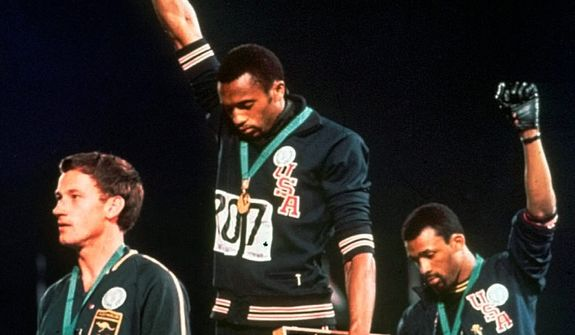 Tommie Smith (center) and John Carlos raise their gloved fists in a human rights protest on Oct. 16, 1968, after accepting their respective gold and bronze medals at the Olympic Games in Mexico City. (ASSOCIATED PRESS)