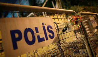 A bouquet is left on the police barriers blocking the road to Saudi Arabia's Consulate in Istanbul, on Monday. Turkish crime scene investigators entered the consulate nearly two weeks after the disappearance and alleged slaying of Saudi writer Jamal Khashoggi. (ASSOCIATED PRESS)