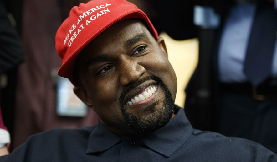 Rapper Kanye West smiles as he listens to a question from a reporter during a meeting in the Oval Office of the White House with President Donald Trump, Thursday, Oct. 11, 2018, in Washington. (AP Photo/Evan Vucci)