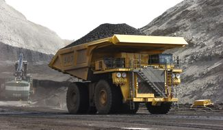 In this April 4, 2013, file photo, a mining dumper truck hauls coal at Cloud Peak Energy's Spring Creek strip mine near Decker, Mont. The Trump administration is considering using West Coast military bases or other federal properties as transit points for shipments of U.S. coal and natural gas to Asia. (AP Photo/Matthew Brown, File)