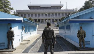 In this April 18, 2018 file photo, two South Korean soldiers, center and left, and U.S. soldier, right, stand in the southern side during a press tour at the border village of Panmunjom in the Demilitarized Zone, South Korea. North and South Korea and the U.S.-led United Nations Command on Tuesday, Oct. 16, 2018, are meeting to discuss efforts to disarm a military zone the rivals control within their shared border under a peace agreement between the Koreas. (AP Photo/Lee Jin-man, File)