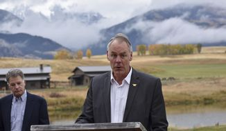 In this Oct. 8, 2018 photo, U.S. Interior Secretary Ryan Zinke announces a ban on mining claims north of Yellowstone National Park as K.C. Walsh, left, president of Simms Fishing Products, listens near Emigrant, Mont. The Trump administration is considering using West Coast military bases or other federal properties as transit points for shipments of U.S. coal and natural gas to Asia as officials seek to bolster the domestic energy industry and circumvent environmental opposition to fossil fuel exports, according to Zinke and two Republican lawmakers. (AP Photo/Matthew Brown)