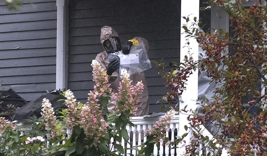 A person in a hazmat suit appears to be handling a letter that is enclosed in a plastic bag in Bangor, Maine, Monday, Oct. 15, 2018. A hazardous materials team was called Monday to investigate a suspicious letter sent to the home of Republican Sen. Susan Collins, officials said. Law enforcement officials were analyzing the contents of the letter. An FBI spokeswoman said Monday evening that preliminary tests on the envelope indicated there was no threat to the public. (Gabor Degre/The Bangor Daily News via AP)