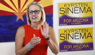 FILE--In this Aug. 28, 2018, file photo, Rep. Kyrsten Sinema, D-Ariz., talks to campaign volunteers at a Democratic campaign office on primary election day in Phoenix. Republican Martha McSally and Sinema will confront each other at a debate Monday, Oct. 15, 2018, in a race for the seat being vacated by retiring Sen. Jeff Flake, which could determine which party controls the Senate next year. (AP Photo/Ross D. Franklin, file)