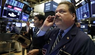 Trader John Santiago, right, works on the floor of the New York Stock Exchange, Monday, Oct. 15, 2018. Stocks are opening mostly lower as technology companies continue to fall. (AP Photo/Richard Drew)