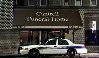 A Detroit Police vehicle is parked outside the Cantrell Funeral Home in Detroit on Friday, Oct. 12, 2018. Police said an anonymously written letter led inspectors to find the decomposed remains of 11 infants hidden in a ceiling compartment of the shuttered funeral home. (Junfu Han/Detroit Free Press via AP)