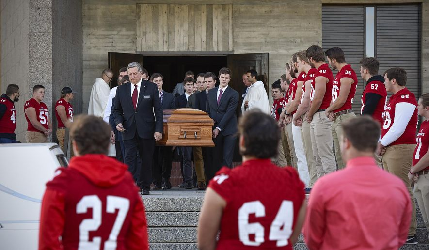 St. John's University football players stand solemnly as the casket of long time St. John's University football coach John Gagliardi is carried to a hearse Monday, Oct. 15, 2018, at the St. John's Abbey in Collegeville, Minn. Using unconventional methods at the small private university in Minnesota, Gagliardi won more football games than anybody who has ever coached in college. Gagliardi died Sunday, Oct. 7, 2018, at the age of 91. (Jason Wachter/St. Cloud Times via AP)