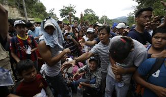 Honduran migrants receive free water from Guatemalan police at the Honduran border crossing that connects with Agua Caliente, Guatemala, Monday, Oct. 15, 2018. Hundreds of Honduran migrants were eventually allowed to cross at the Guatemalan border under a broiling sun Monday hoping to make it to new lives in the United States, far from the poverty and violence of their home nation. (AP Photo/Moises Castillo)
