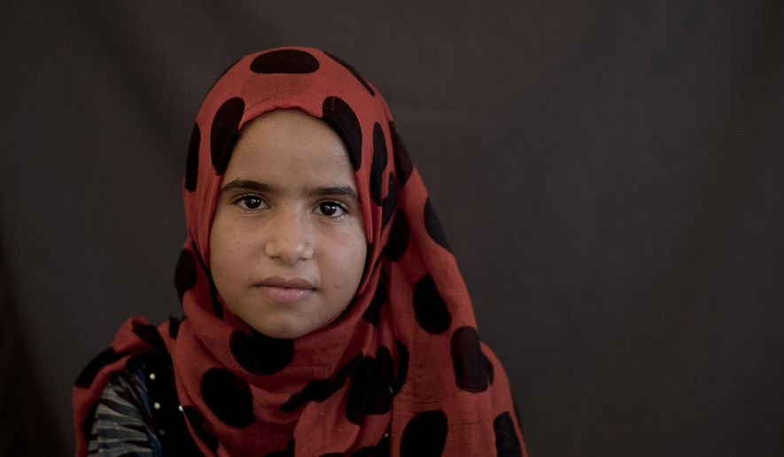 In this Aug. 28, 2018, photo, Dawlat Suleiman poses for a portrait in her family's tent at Dakuk Camp, near Kirkuk, Iraq. At 12 years old, Dawlat has lost her childhood. With her parents gone, she must serve as a replacement mother caring for five of her siblings, a family of kids fending for themselves amid the destruction of post-war Iraq. (AP Photo/Maya Alleruzzo)