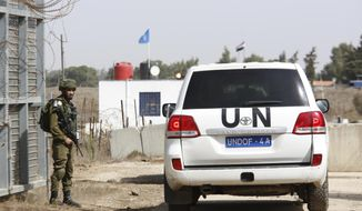 An Israeli soldier opens the border gates as an UN vehicle enters Syria in Quneitra crossing in the Israeli controlled Golan, Monday, Oct. 15, 2018. The crossing between Syria and the Israeli-occupied Golan Heights reopened for U.N. observers who had left the area four years ago because of the fighting there. (AP Photo/Ariel Schalit)