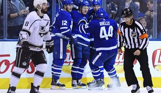 Toronto Maple Leafs right wing Kasperi Kapanen (24) celebrates his goal with teammates Patrick Marleau (12), Auston Matthews (34) and Morgan Rielly (44) as Los Angeles Kings defenseman Drew Doughty (8) looks on during third period NHL hockey action in Toronto on Monday, Oct. 15, 2018. (Nathan Denette/The Canadian Press via AP)