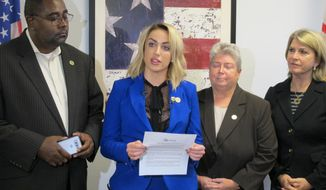 """Meagan Simonaire, a Maryland state lawmaker, announces she is switching parties from Republican to Democrat on Monday, Oct. 15, 2018, in Annapolis, Md., partly because of President Donald Trump. Simonaire said she """"can no longer remain a part of a party that condones his rhetoric"""" against women and minorities. Simonaire is standing with Del. Darryl Barnes, left, Del. Bonnie Cullison, and Kathleen Matthews, far left, who chairs the Maryland Democratic Party. (AP Photo/Brian Witte)"""