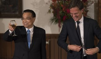 Dutch Prime Minister Mark Rutte gets up as Chinese Premier Li Keqiang proposes a toast during luncheon in The Hague, Netherlands, Monday, Oct. 15, 2018. (AP Photo/Peter Dejong)