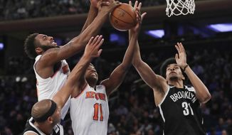 New York Knicks' Mitchell Robinson, left, and Frank Ntilikina, center, and Brooklyn Nets' Jarrett Allen (31) reach for a rebound during the first half of a preseason NBA basketball game Friday, Oct. 12, 2018, in New York. (AP Photo/Frank Franklin II)
