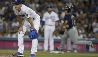 Los Angeles Dodgers starting pitcher Walker Buehler reacts after giving up a double to Milwaukee Brewers' Erik Kratz during the seventh inning of Game 3 of the National League Championship Series baseball game Monday, Oct. 15, 2018, in Los Angeles. (AP Photo/Jae Hong)