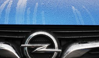 FILE - This Thursday, Nov. 9, 2017 file photo shows an Opel logo of an Opel Grandland at the Opel headquarters in Ruesselsheim, Germany. German prosecutors said Monday Oct. 15, 2018, that law enforcement officials have conducted searches at automaker Opel as part of an investigation into suspected manipulation of diesel emissions. (AP Photo/Michael Probst, File)