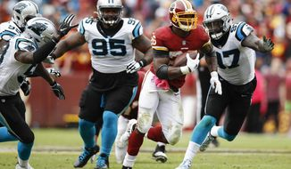 Washington Redskins running back Adrian Peterson (26) carries the ball past Carolina Panthers nose tackle Dontari Poe (95) and defensive end Mario Addison (97) during the second half of an NFL football game, Sunday, Oct. 14, 2018, in Landover, Md. (AP Photo/Patrick Semansky)