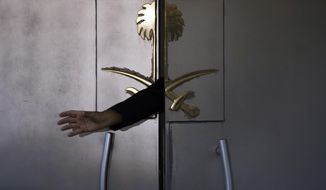FILE- In this Friday, Oct. 12, 2018 file photo, a security guard reaches out his hand from the entrance of the Saudi Arabia's consulate in Istanbul, Turkey. (AP Photo/Petros Giannakouris)