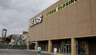 In this July 8, 2017, file photo people walk into a Sears store slated for closing that is next to a mall that is being torn down in Overland Park, Kan. Sears has filed for Chapter 11 bankruptcy protection Monday, Oct. 15, 2018, buckling under its massive debt load and staggering losses. The company once dominated the American landscape, but whether a smaller Sears can be viable remains in question. (AP Photo/Charlie Riedel, File)