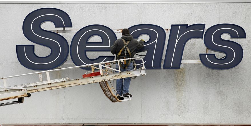 FILE - In this Feb. 13, 2012 file photo, a worker repairs a sign outside the Sears Grand store in Solon, Ohio. Sears has filed for Chapter 11 bankruptcy protection Monday, Oct. 15, 2018, buckling under its massive debt load and staggering losses. The company once dominated the American landscape, but whether a smaller Sears can be viable remains in question. (AP Photo/Amy Sancetta, File)