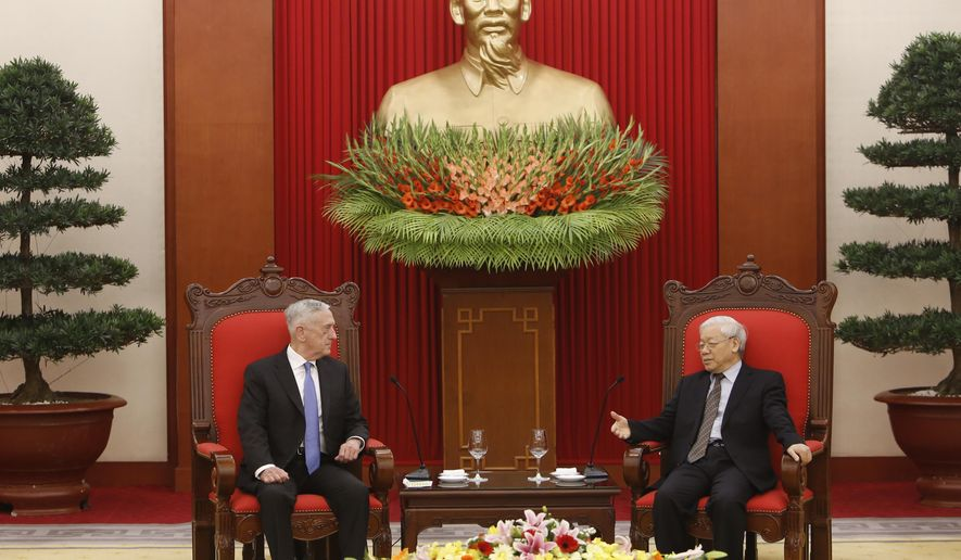 FILE - In this  Jan. 25, 2018, file photo, U.S. Secretary of Defense Jim Mattis, left, listens during talks with Vietnam's Communist Party General Secretary Nguyen Phu Trong in Hanoi, Vietnam. Mattis is planning to make his second visit to Vietnam this year, signaling how vigorously the Trump administration is trying to counter China's military assertiveness in the South China Sea by building up relations with smaller nations in the region. (AP Photo/Tran Van Minh, File)