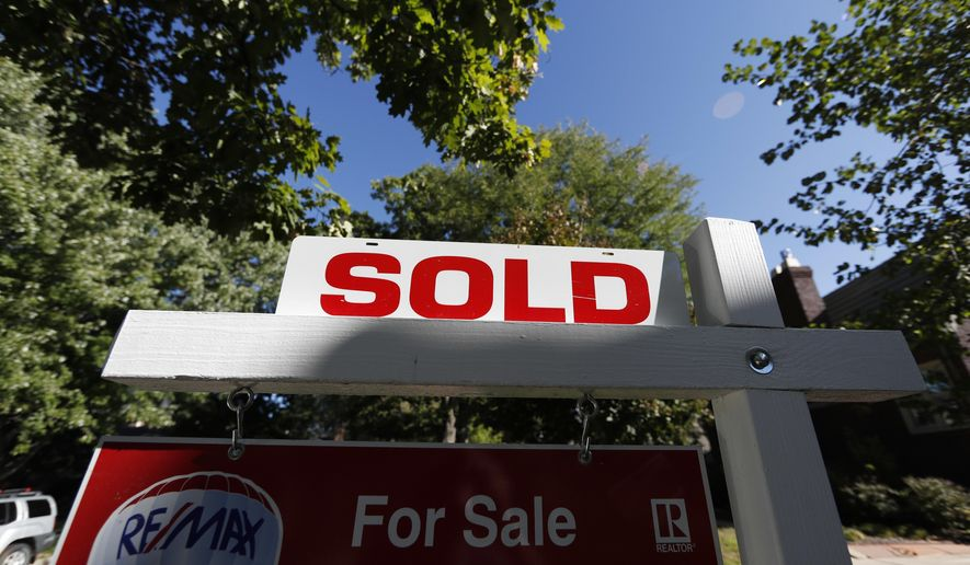 FILE- In this Thursday, Aug. 30, 2018, photo a sale placard tops a sale sign stand outside a home on the market in Denver. The National Association of Realtors serves up its latest monthly tally of home sales Friday, Oct. 19. (AP Photo/David Zalubowski, File)