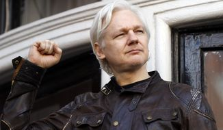 In this May 19, 2017 file photo, WikiLeaks founder Julian Assange greets supporters outside the Ecuadorian embassy in London, where he has been in self imposed exile since 2012. (AP Photo/Frank Augstein, file)