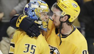 Nashville Predators center Ryan Johansen (92) and goaltender Pekka Rinne (35), of Finland, celebrate a win over the Minnesota Wild in an NHL hockey game Monday, Oct. 15, 2018, in Nashville, Tenn. The Predators won 4-2. (AP Photo/Mark Humphrey)
