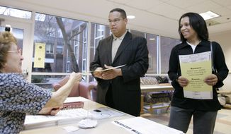 Stete Rep. Keith Ellison, center, a Democratic candidate for U.S. House, and his wife, Kim, right, get their ballots prior to voting in Minneapolis, Minn., Tuesday, Nov. 7, 2006. (AP Photo/Ann Heisenfelt)