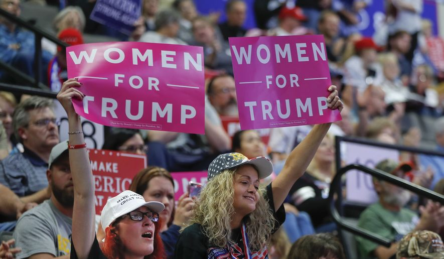 """Supporters hold up """"Women for Trump"""" signs as they listen to President Donald Trump speak at a campaign rally at WesBanco Arena, Saturday, Sept. 29, 2018, in Wheeling, WV. (AP Photo/Pablo Martinez Monsivais)"""