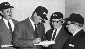 Bat gets autograph of Ted Williams in Chicago on Dec. 27, 1960, just like it might have if Ted were still a member of the Boston Red Sox. The retired Williams posed after signing a contract with a mail order firm, where he will serve as adviser in promotion and marketing of sports equipment. From left, George H. Struthers, vice president of Sears; Williams; Crowdus Baker, president; and Charles Kellstadt, board chairman. (AP Photo) **FILE**