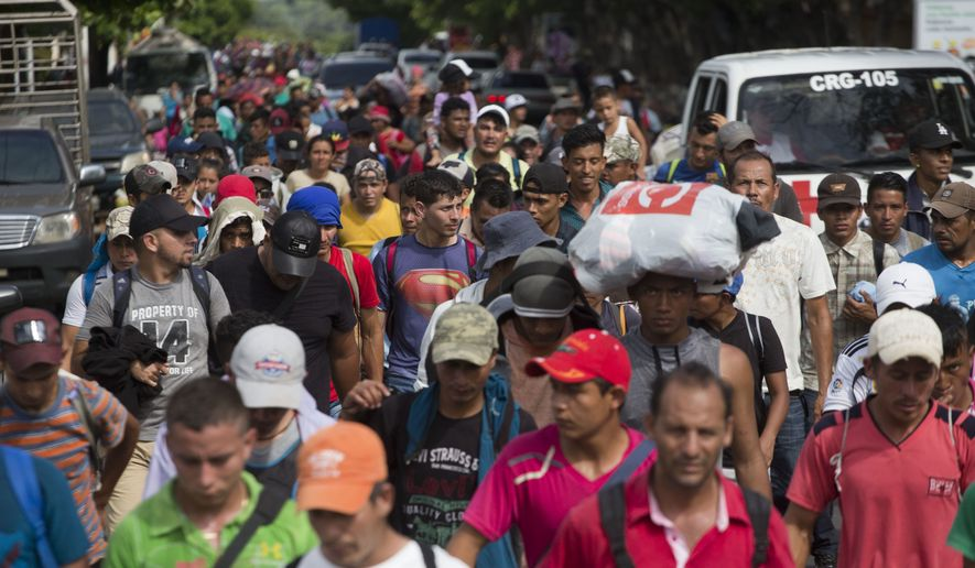 Honduran migrants walk toward the U.S. as they arrive at Chiquimula, Guatemala, Tuesday, Oct. 16, 2018. U.S. President Donald Trump threatened on Tuesday to cut aid to Honduras if it doesn't stop the impromptu caravan of migrants, but it remains unclear if governments in the region can summon the political will to physically halt the determined border-crossers. (AP Photo/Moises Castillo)