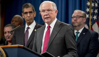 Attorney General Jeff Sessions, center, accompanied by Drug Enforcement Administration Acting Administrator Uttam Dhillon, center left, and other officials from the State Department, Treasury Department, Internal Revenue Service and Immigration and Customs Enforcement, speaks at a news conference to announce enforcement efforts against Cartel Jalisco Nueva Generacion, Tuesday, Oct. 16, 2018, at the Justice Department in Washington. (AP Photo/Andrew Harnik)