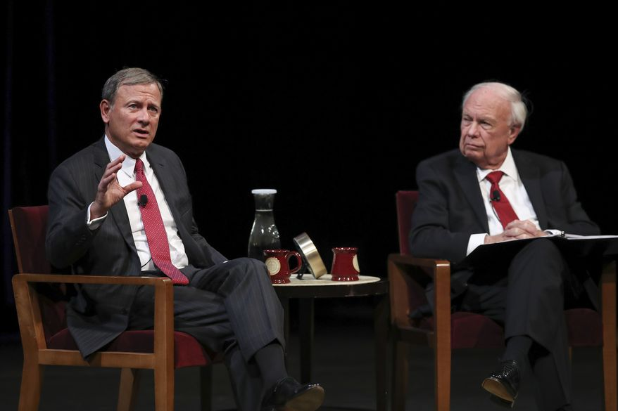 U.S. Supreme Court Chief Justice John G. Roberts, Jr., left, answers a student's question following his conversation with Professor Robert A. Stein Tuesday, Oct. 16, 2018 at Northrop Auditorium in Minneapolis. (Jeff Wheeler/Star Tribune via AP)