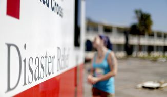 Crystal Williams receives food from the Red Cross outside a damaged motel, Tuesday, Oct. 16, 2018, in Panama City, Fla., where many residents continue to live in the aftermath of Hurricane Michael. (AP Photo/David Goldman)