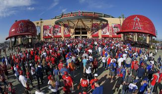 FILE - In this Monday, April 4, 2016 file photo, Fans line up outside Angel Stadium of Anaheim for an opening day baseball game between the Los Angeles Angels and the Chicago Cubs in Los Angeles. The Los Angeles Angels have opted out of their Angel Stadium lease with the city of Anaheim. The Angels informed the city of their decision Tuesday, Oct. 16, 2018.  (AP Photo/Mark J. Terrill, File)