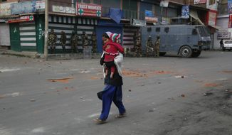 A Kashmiri woman carries a child and walks towards a hospital, outside a poling station during the fourth phase of local elections in Srinagar, Indian controlled Kashmir, Tuesday, Oct. 16, 2018. India says the polls are a vital grass roots exercise to boost development and address civic issues. Political separatist leaders and armed rebel groups who challenge India's sovereignty over Kashmir have called for a boycott, saying the polls are an illegitimate exercise under military occupation. Authorities have deployed more than 40,000 additional soldiers in what is already one of world's most heavily militarised regions to guard the voting for urban and village councils. (AP Photo/Mukhtar Khan)