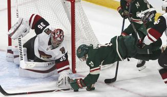 Minnesota Wild's Zach Parise, right, dives for the puck as Arizona Coyotes' goalie Darcy Kuemper reaches for it in the second period of an NHL hockey game Tuesday, Oct. 16, 2018, in St. Paul, Minn. (AP Photo/Jim Mone)