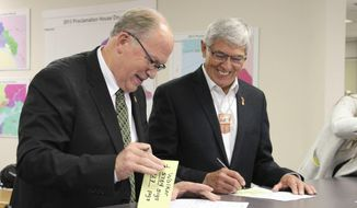 """File - In this Aug. 20, 2018 file photo, Alaska Gov. Bill Walker, left, and Lt. Gov. Byron Mallott sign forms at the Division of Elections office in Anchorage, Alaska after the two men submitted signatures to get their ticket on the November general election ballot. The governor of Alaska says Lt. Gov. Byron Mallott has resigned over unspecified """"inappropriate comments."""" The move upends what was already a difficult re-election fight for Gov. Bill Walker. Mallott's decision was announced Tuesday, Oct. 16, 2018, shortly after Walker participated in a debate in Anchorage. (AP Photo/Mark Thiessen, File)"""