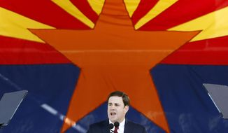 FILE - In this Jan. 5, 2015, file photo, Republican Arizona Gov. Doug Ducey addresses the crowd after being sworn in during inauguration ceremonies at the Arizona Capitol in Phoenix. Comfortable that he has a solid lead in his re-election bid, Republican Arizona Gov. Doug Ducey is risking further angering the state's teachers by forcefully backing a measure that would massively expand the state's private school voucher system. The Republican governor has come out strongly this month in support of the school voucher plan, which is on the ballot as Proposition 305. A yes vote allows the vouchers system to expand, while a no vote rejects it. (AP Photo/Ross D. Franklin, File)