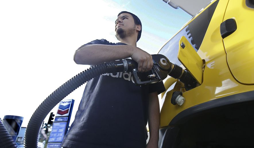 In this Oct. 30, 2017, file photo, Cristian Rodriguez fuels his vehicle in Sacramento, Calif. (AP Photo/Rich Pedroncelli, File)