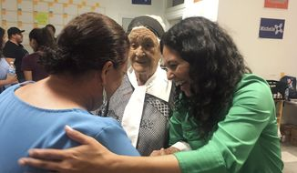 In this Oct. 3, 2018 photo, Democratic Congressional hopeful Xochitl Torres Small, right, greets supporters at the opening of her Sunland Park, New Mexico office. Federal documents show Torres Small raised more than three times as much money last quarter as Republican Yvette Herrell in a closely watched U.S. House race in southern New Mexico. (AP Photo/Russell Contreras)