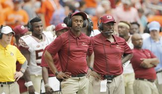 FILE - In this Sept. 15, 2018, file photo, Florida State head coach Willie Taggart, left, watches a replay beside defensive coordinator Harlon Barnett in the fourth quarter of an NCAA college football game against Syracuse, in Syracuse, N.Y. Florida State has returned to practice field following a bye week and in the wake of Hurricane Michael after a rocky start under first-year football coach Willie Taggart. The Seminoles, who are preparing for Saturday's ACC matchup with Wake Forest, pitched in to help storm victims when they returned to Tallahassee on Saturday. (AP Photo/Nick Lisi, File)