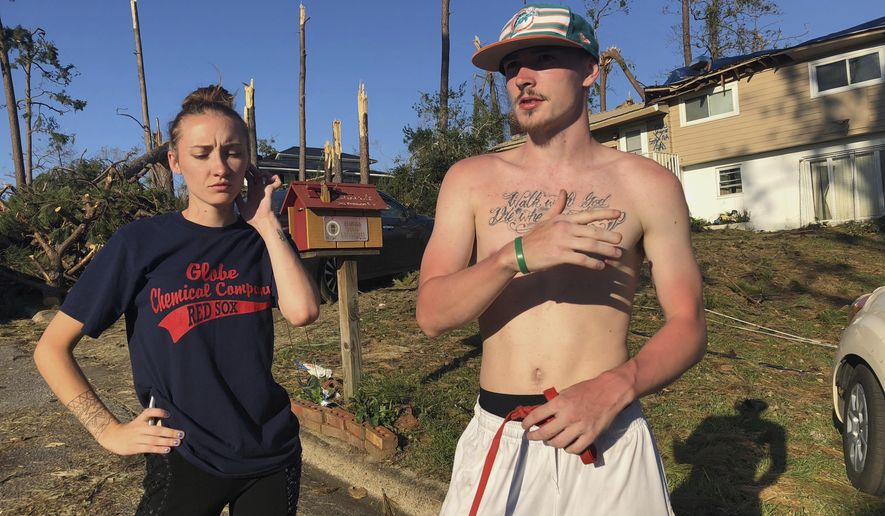 In this Oct. 10, 2018 photo, Shauna Benefield and Alex Edwards stand in front of their house in Marianna, Fla., which was damaged by fallen trees during Hurricane Michael. Benefield, 20, and her boyfriend, Edwards, 21, live just north of Marianna's historic downtown in his family's home and they didn't stock up. After the storm cleared, Edwards found himself driving 50 miles to DeFuniak Springs to get water, food and gas. There was nowhere nearby to get any in the immediate aftermath.  (AP Photo/Brendan Farrington)