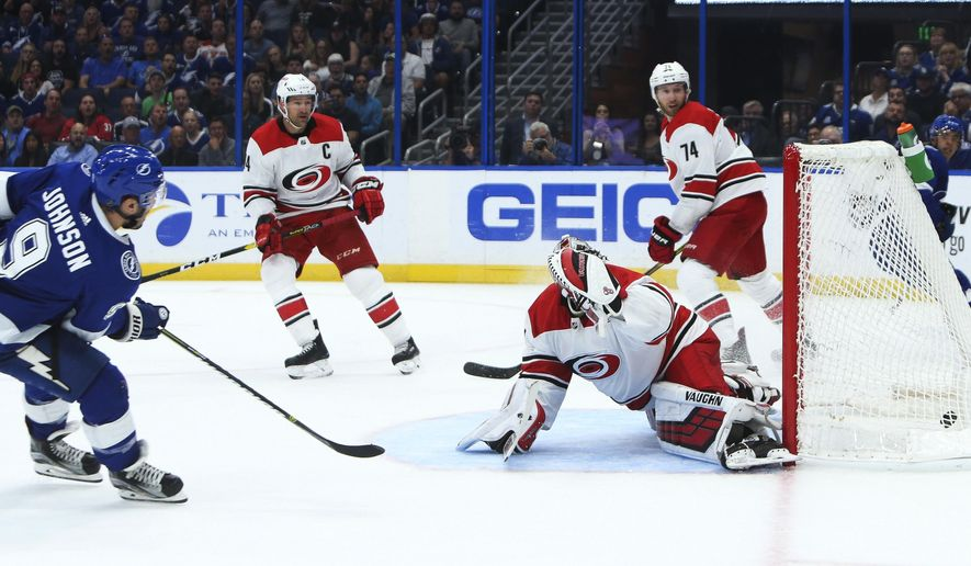 Tampa Bay Lightning center Tyler Johnson (9) gets a pass from right wing Mathieu Joseph (7) and scores a short-handed goal against Carolina Hurricanes goaltender Petr Mrazek (34) to tie the score at 1 to 1 during the first period action of an NHL hockey game, Tuesday, Oct. 16, 2018, in Tampa, Fla. (Dirk Shadd/Tampa Bay Times via AP)