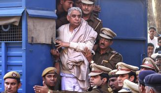 FILE - In this Nov. 20, 2014 file photo, controversial religious leader Sant Rampal stands by the door of a police van as he is brought to a court, surrounded by police personnel in Chandigarh, India. A court in northern India on Tuesday, oct. 16, 2018, has sentenced the Hindu guru and 14 followers to life imprisonment in the deaths of four women and a child at his sprawling ashram. Rampal was arrested in 2014 following a days-long standoff between law enforcers and his supporters in which six people died and hundreds were injured. (AP Photo/Kapil Sethi, File)